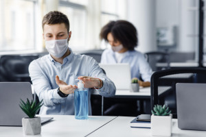 Rules for safety health during coronavirus outbreak. Man in protective mask treat his hands with antiseptic at workplace with laptop in interior of modern coworking office, copy space